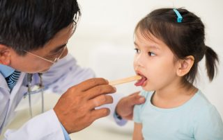 a doctor examining a child who has enlarged tonsils